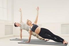 Posa della sponda di yoga di addestramento della donna e dell'uomo Immagine Stock
