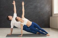 Posa della sponda di yoga di addestramento della donna e dell'uomo Fotografia Stock Libera da Diritti