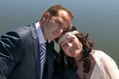 Posa delle coppie di cerimonia nuziale con la parte inferiore di lago Fotografia Stock