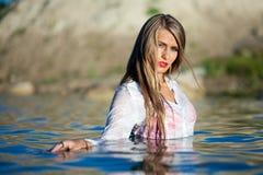 Posa di modello caucasica in camicia bianca bagnata in acqua Fotografia Stock Libera da Diritti