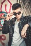 Posa di modello del giovane uomo alla moda in bomber ed occhiali da sole Fotografie Stock Libere da Diritti