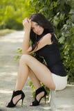 Posa di modello della donna castana attraente nel parco di primavera, porto pieno Fotografia Stock