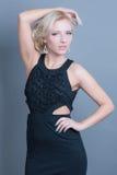 Posa di modello della giovane bella donna bionda in vestito nero Fotografia Stock