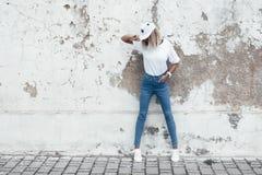 Posa di modello in maglietta normale contro la parete della via Fotografia Stock Libera da Diritti