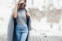Posa di modello in maglietta normale contro la parete della via Immagine Stock
