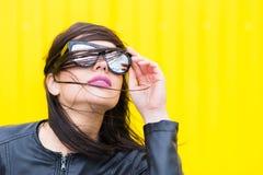 Posa di modello per il fotografo su un fondo giallo Immagine Stock