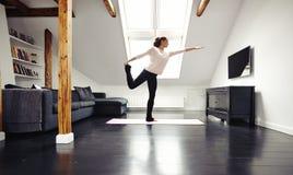 Posa di pratica del guerriero di yoga della giovane signora adatta a casa - Fotografia Stock