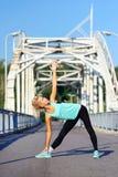 Posa di pratica di yoga del triangolo della donna allegra Immagini Stock Libere da Diritti