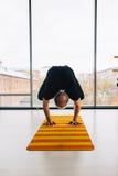 Posa di pratica di yoga dell'uomo all'interno, vista panoramica della città a fondo Immagini Stock
