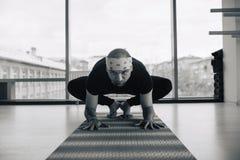 Posa di pratica di yoga dell'uomo all'interno, vista panoramica della città a fondo Immagini Stock Libere da Diritti