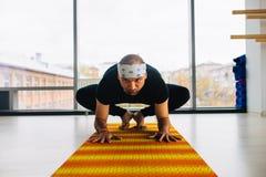 Posa di pratica di yoga dell'uomo all'interno, vista panoramica della città a fondo Fotografia Stock Libera da Diritti