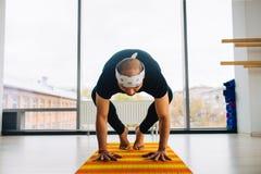 Posa di pratica di yoga dell'uomo all'interno, vista panoramica della città a fondo Immagine Stock Libera da Diritti
