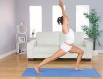 Posa di pratica di yoga della donna esile sportiva per l'allungamento del suo corpo Fotografie Stock Libere da Diritti