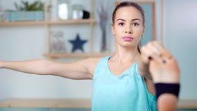 Posa di pratica di yoga della bella giovane donna sportiva del colpo medio durante l'allungamento della gamba che fa equilibrio stock footage