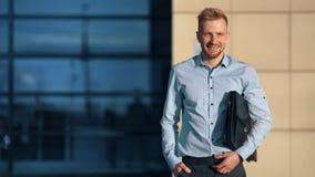 Posa di tenuta maschio sorridente della cartella di affari di modo all'aperto al tramonto sull'edificio per uffici archivi video