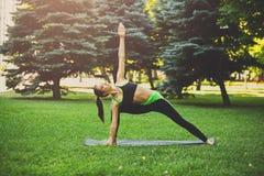 Posa di yoga di addestramento della donna all'aperto Fotografia Stock