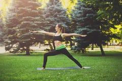 Posa di yoga di addestramento della donna all'aperto Immagini Stock