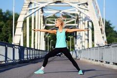 Posa di yoga del guerriero sul fondo d'acciaio del ponte Immagini Stock