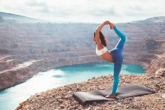 Posa di yoga di addestramento della ragazza all'aperto Immagine Stock