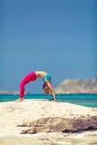 Posa di yoga, esercizio adatto della donna sulla spiaggia Fotografie Stock Libere da Diritti