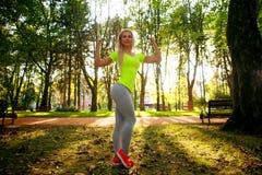 Posa esile sportiva della donna nel parco verde della città di estate Immagini Stock Libere da Diritti