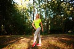Posa esile sportiva della donna nel parco verde della città di estate Fotografia Stock