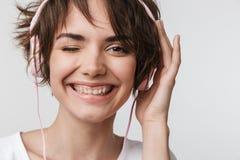 Posa felice emozionante graziosa della donna isolata sopra musica d'ascolto del fondo bianco della parete con le cuffie immagini stock libere da diritti