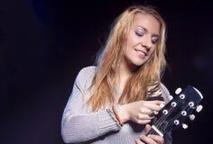 Posa femminile bionda caucasica con la chitarra contro il nero Immagine Stock