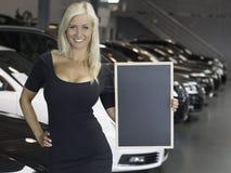 Posa femminile con il segno davanti alle nuove automobili Fotografie Stock Libere da Diritti