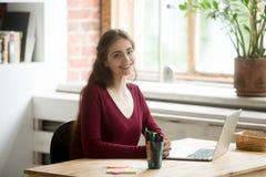 Posa femminile sorridente mentre lavorando al computer portatile Fotografia Stock Libera da Diritti