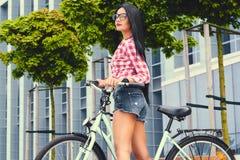 Posa femminile su una bicicletta sopra il fondo moderno della costruzione fotografia stock