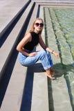 Posa girt pantaloni a vita bassa vicino ad una fontana Fotografie Stock Libere da Diritti