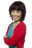 Posa laterale della donna asiatica sorridente, braccia attraversate immagine stock libera da diritti