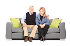 Posa matura adorabile delle coppie messa sul sofà Immagine Stock