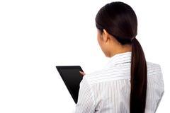 Posa posteriore di un dispositivo di cuscinetto di funzionamento di tocco della donna Immagini Stock