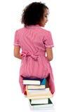 Posa posteriore di una ragazza che si siede su un mucchio dei libri Immagine Stock