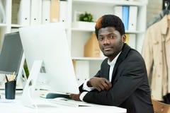 Posa professionale afroamericana nell'ufficio Immagine Stock