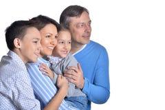 Posa sorridente felice di famiglia di quattro isolata su fondo bianco fotografia stock