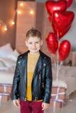 Posa teenager dei pantaloni a vita bassa bei con il baloon rosso del cuore in studio Giovane in camicia gialla che va alla data s Immagine Stock Libera da Diritti