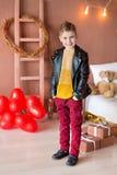 Posa teenager dei pantaloni a vita bassa bei con il baloon rosso del cuore in studio Giovane in camicia gialla che va alla data s Fotografia Stock Libera da Diritti