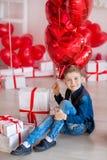 Posa teenager dei pantaloni a vita bassa bei con il baloon rosso del cuore in studio Giovane in camicia gialla che va alla data s Fotografia Stock
