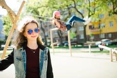 Posa teenager e bambino della ragazza di età in cappuccio rosa che oscilla sul campo da giuoco nel fondo immagini stock libere da diritti