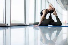 Posa zoppicanta del piccione di re La giovane donna esile nella classe di yoga che fa il bello asana si esercita Stile di vita sa Immagine Stock
