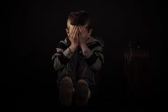 Posadzona Okaleczająca chłopiec Zakrywa jego Przeciw czerni twarz Zdjęcia Stock