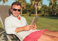 Posadzony mężczyzna trzyma pastylka ochraniacza komputerowy w okularach przeciwsłonecznych Obrazy Royalty Free