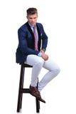 Posadzony młody biznesowy mężczyzna z ręką na jego biodrze Obrazy Royalty Free