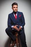 Posadzony młody elegancki mężczyzna patrzeje daleko od w kostiumu i krawacie zdjęcia royalty free