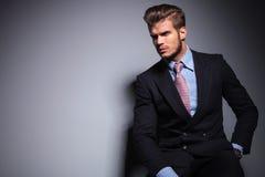 Posadzony młody moda model w kostiumu patrzeje daleko od obrazy stock