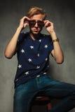 Posadzony moda mężczyzna bierze daleko jego okulary przeciwsłonecznych obraz stock