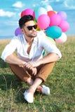 Posadzony przypadkowy mężczyzna z balonów spojrzeniami daleko od Zdjęcie Stock